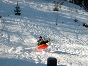 A man on a snow tube in Glenwood Springs, home to some of the best sledding in Colorado