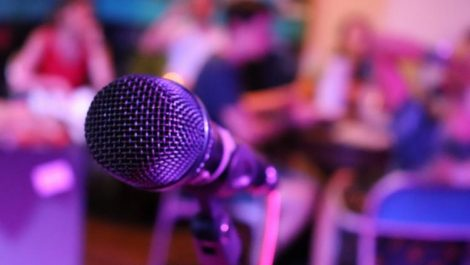 A microphone and audience in a room at a Denver karaoke establishment
