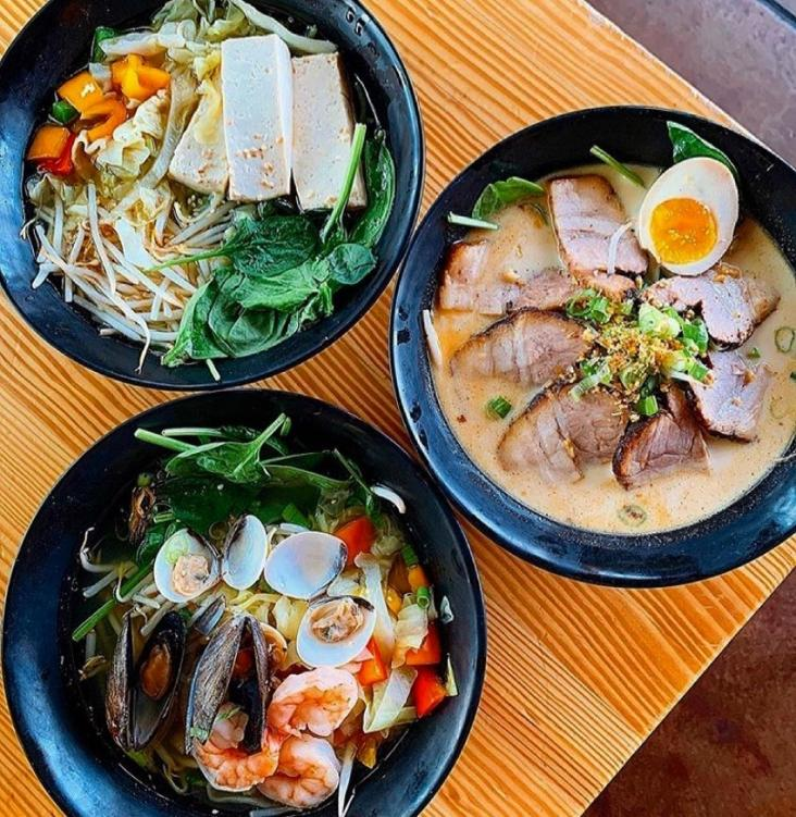 Three bowls of ramen sitting on top of a table