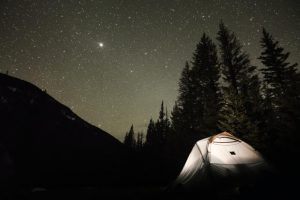 An illuminated tent at one of the free campsites in Colorado, under a night sky