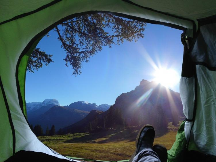 A person relaxing in their tent at a free campsite in Colorado, with the tent door open and the sun shining in behind the mountains