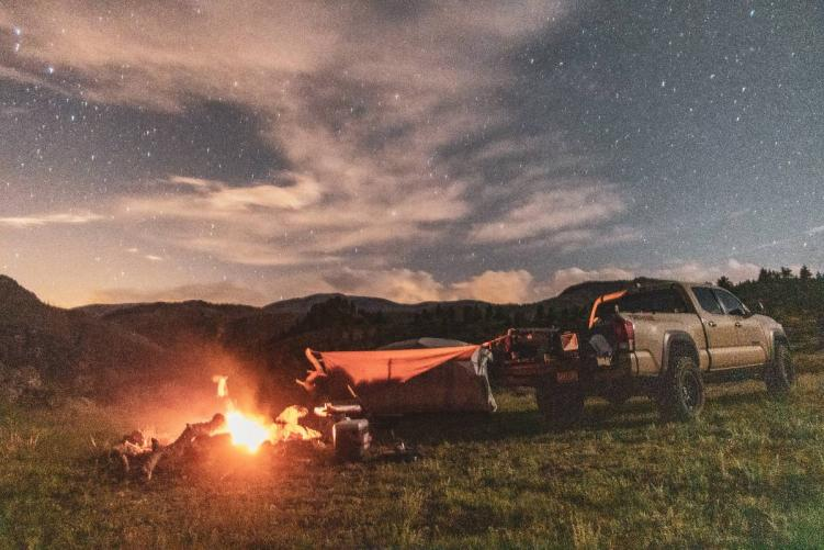 A tan pickup truck, tent, and campfire under a night sky at one of the best free campsites in Colorado
